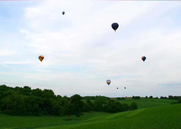 Balloons from the hot air balloon rally float over fields
