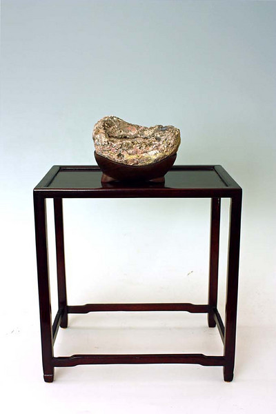 Suiseki are commonly displayed on a flat board (ji-ita).  However, this stone cannot be appreciated that way, and looks much better if raised up on a display stand (shoku).  <br /> <br /> This is our preferred display.  The simplified form of this shoku, with the large empty space below, allows us to focus on the suiseki and gives it a delicate appearance.