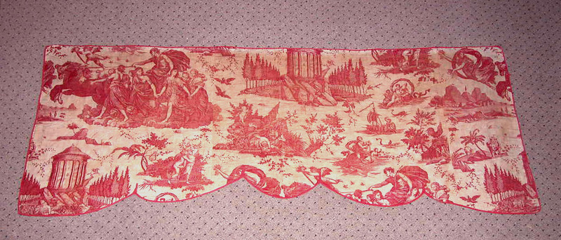 "An 18th century quilted bed valence, the front of copper plate printed toile, madder-mordant, with scenes from the myth of Apollo.  The material is probably English, last quarter of the 18th century.   A similar textile printed with scenes from the Odyssey is in the collection of the Victoria and Albert Museum, London, illustrated in F. Montgomery's PRINTED TEXTILES. The curtain has a plain linen backing, is quilted and stuffed with cotton, and has a cut red cotton binding of the same period.  It is 74"" (188 cm) long by 28"" (70.1 cm) wide.  It was found in Maine."