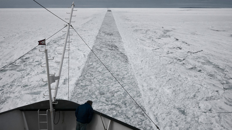 Stuck Fast<br /> The US Coast Guard has created a path for us to follow through the spring ice in Whitefish Bay. The Captain looks down from the bow with concern as we are stuck in the ice.