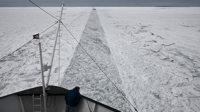 Stuck Fast The US Coast Guard has created a path for us to follow through the spring ice in Whitefish Bay. The Captain looks down from the bow with concern as we are stuck in the ice.