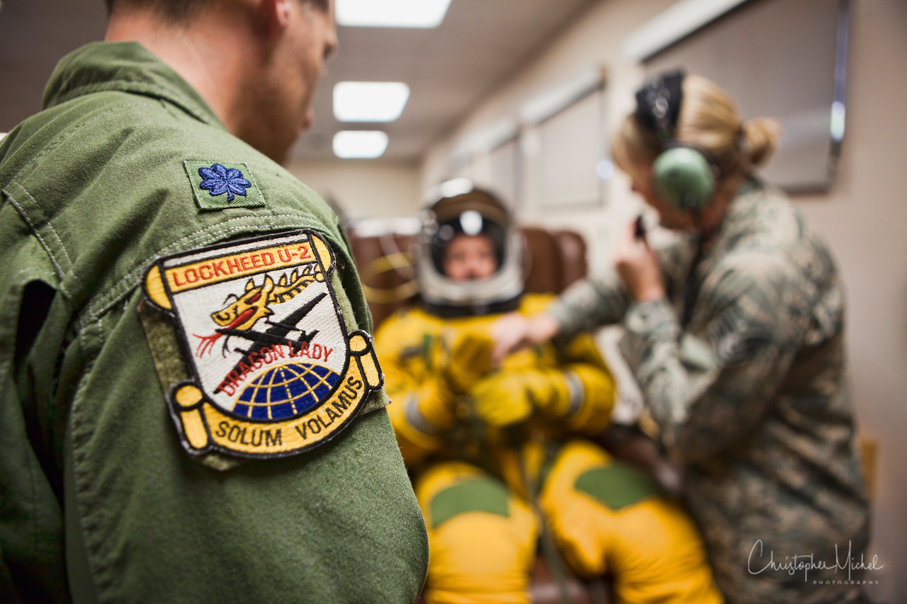 LCOL Joe Santucci, USAF, Commanding Officer of the 99th Reconnaissance Squadron, observes as Christopher Michel suits up.