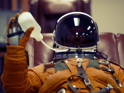 """Christopher Michel trying out the """"tube"""" food & drink in his pressure suit."""