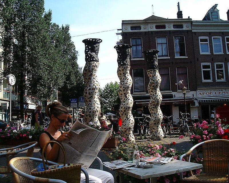 young  Dutch  girl reading under  modern art  statues