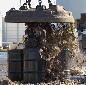 A massive magnet drops the gun metal into large barrels.