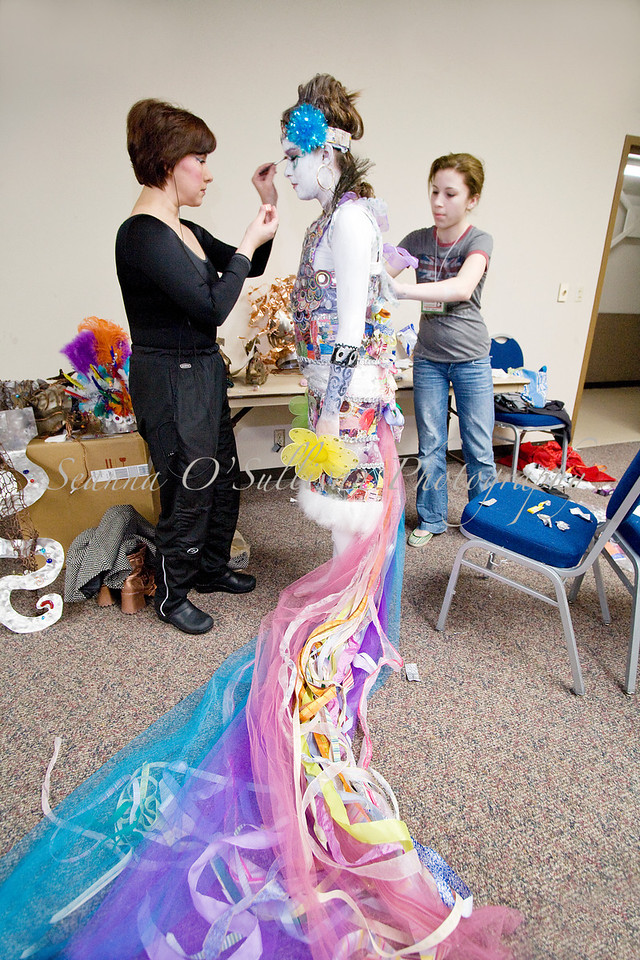 """Artists Rhonda Scott, left, and Rochelle Smallwood, right, work on model Sam Sportel, center, before she models """"Kaleidoscope"""" at the annual Wearable Arts show Saturday, Feb. 14 at Centennial Hall in Juneau, Alaska. The piece, created by Smallwood for her 8th grade ropes project, was made with magazines, ribbons, tulle and a shower curtain. (Photo by Seanna O'Sullivan Photography)"""