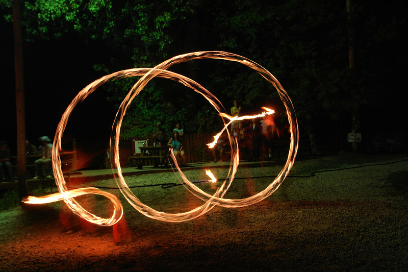 Sometimes, though, a longish exposure brings out both the wonderful pattern created by the spinner and the frozen aspect of the watchers.  This is Keile working his dart, a ball of fire at the end of a 15 foot long rope and chain affair.  What I like is how clearly he is dancing, even though you can't see him.