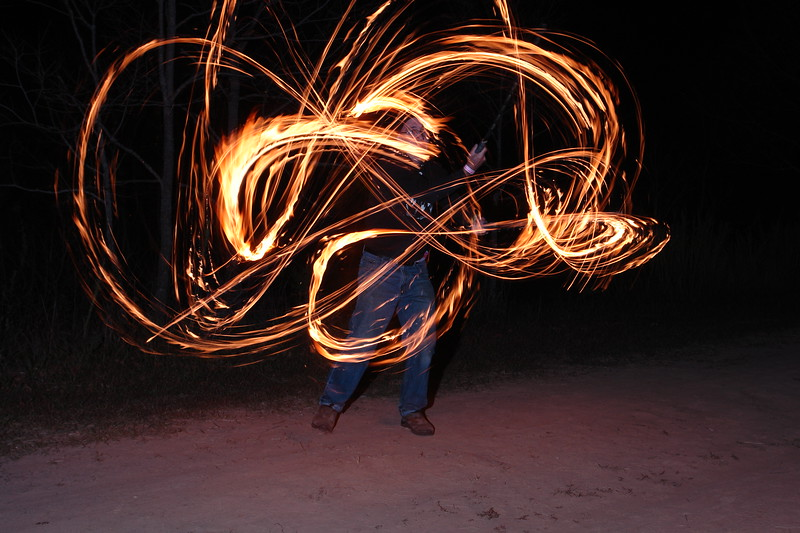 Fire Swords 4901 Before discussing light dancing images in more detail, I want to digress a bit and talk about how I started fire dancing myself and how that led to an unexpected and wonderful collaboration.    I had tried spinning the poi, without fire, and found that it is not a skill that come naturally to me at all.  However, I've been doing fencing and other forms of sword work for many years.  It wasn't long before I decided to build myself a set of fire swords.    I set up the tripod, paced the distance and asked a friend to press the shutter, count to 3 and fire the flash.  Then I lit my swords, started dancing and asked him to fire away.
