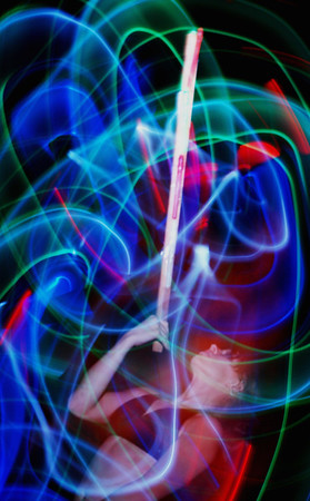 "Light sword 9110  Fire works great outdoors, but indoors, or while practicing, lights work better, or at least safer.  For interesting images, lights often work better too.  So I also built a pair of ""light swords.""  These are simply wooden sticks with battery powered colored lights taped to them.  In October of 1986 I was performed with the Sphyre of Promethus using fire outside and with these colored light swords inside for Lizzie West's  Howloween ball.  Her encouragement and enthusiasm have meant a great deal to both my fire dancing and my photography.    When I got inside I found myself being photographed by all kinds of people as I danced with these light sticks.  One in particular had a full size DSLR on a monopod, but instead of planting it and making a time exposure, he was dancing with it.  He came over to me, quite excited and showed me what he'd captured.  It turned out he had been doing light paintings for 20 some odd years and was greatly inspired by this new way he'd just found of making light paintings.  His name is Peter Anger and the image he made that night he called Equivalent.  One thing led to another and after a couple of  joint studio sessions as well as a session done in the gallery where the show would hang with several dancers on hand and much discussion and further work, we put on a collaborative show at the Davis  Gallery on the Stephens college campus in Columbia, Missouri."