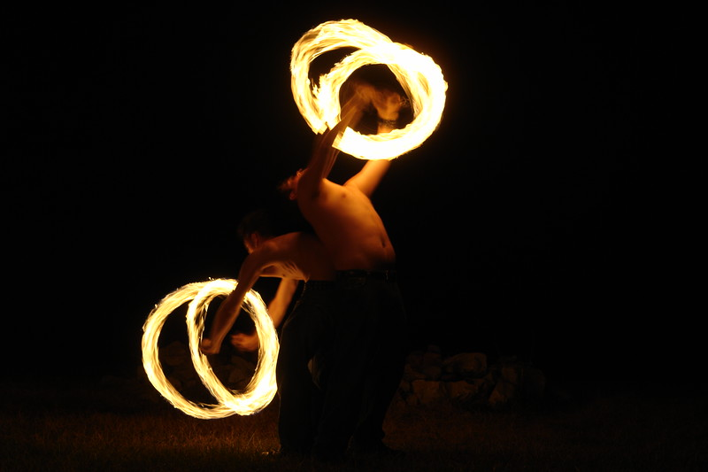 Fire spinners love to see pictures of themselves in action, and it hard to make an exposure the right speed to catch both the spinners and the fire.  Here the pair of them held their position for the 3/4 of a second at F6.3 I used to make the picture.   As you can see, though, the details of the bodies and faces are nearly impossible to make out.  Plus, more often than not, the autofocus will not work under conditions like these, and using the manual focus, either through the viewfinder or peering at the LCD is only marginally better since the dancers are not usually standing in one place long enough to work the manual focus.  So I generally use the only approximately accurate distance indicated on my screen and turn the manual focus dial until the distance indicated is about what I estimate it to be.