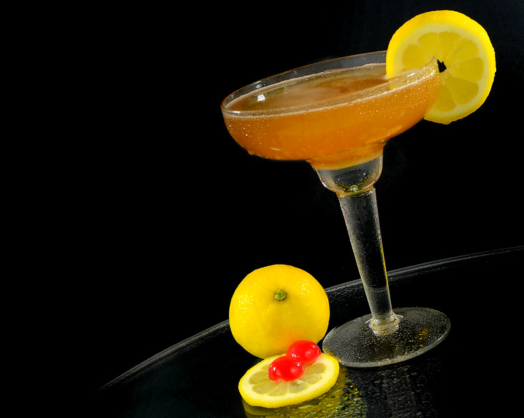 A whisky sour in a coupe glass with a lemon wagon wheel garnish on a round table with dark background. Perspective is tilted. Lemon a cherries on side