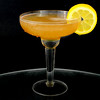 A whisky sour in a coupe glass with a lemon wagon wheel garnish on a dark background