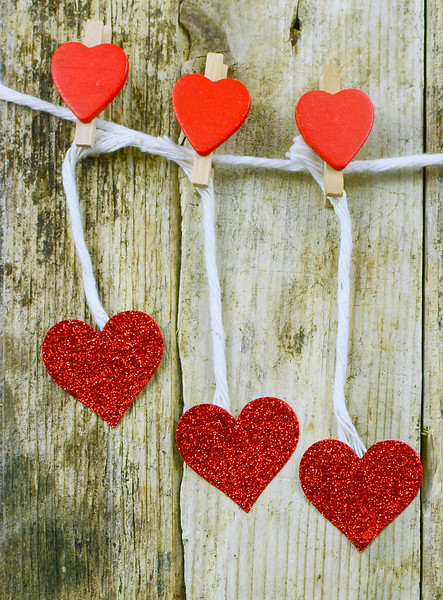 Sparkly red hearts handing from decorated clothespins by string in front of rustic wooden background for Valentine's Day. Vertical composition.