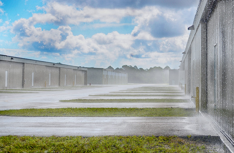 Rain falling on the ramp of a rural airport between small hangars whose doors are all closed. The sky is blue and partly cloudy. The rain is splashing on the asphalt