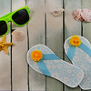 Cute, paper craft flip-flops that are ocean blue with sunny silk flower decoration. Summer decorations like seashells and starfish added.