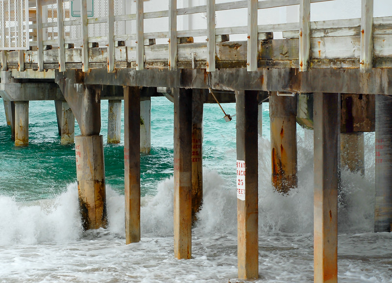 Tourquoise waves breaking on a beach next to a pier. Signs posted saying stay back