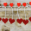 Sparkly red hearts handing from decorated clothespins by string in front of rustic wooden background for Valentine's Day