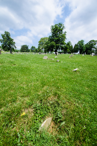 This head stone is almost completely buried by the eroding land on this hill.