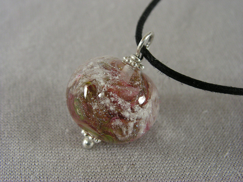 Pink and green Stardust Memories series bead, with sterling silver wirework.