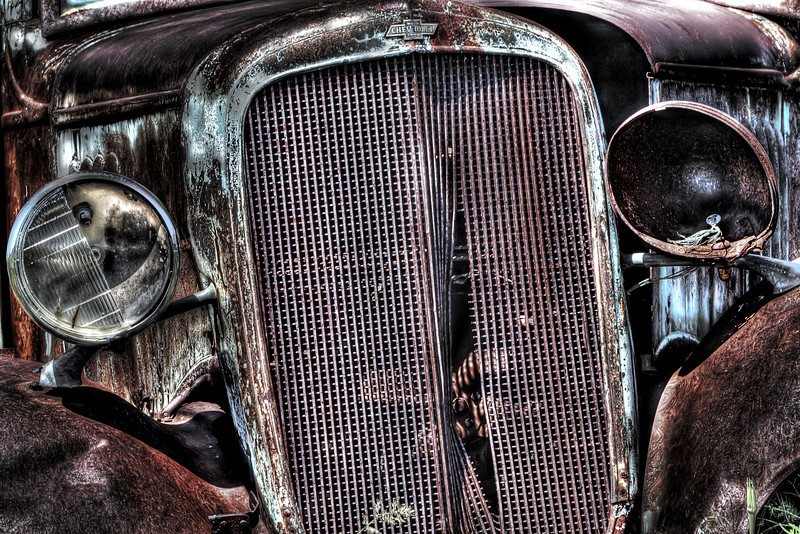 "The grill of an old Chevy pickup laying in a field in Shaniko, Oregon.<br /> By Brett Downen<br /> <br /> Float Mounted MetalPrint<br /> Available sizes: 4"" x 6"", 8"" x 12"", 16"" x 24"". 24"" x 36"""
