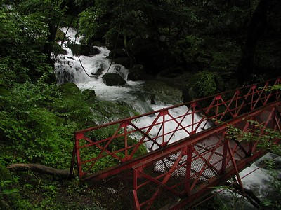 Red bridge over mountain stream