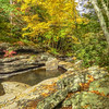 An autumn scene of a small  stream flowing through large rocks.A beautiful fall day.
