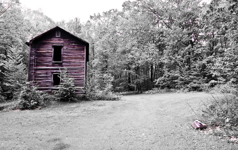 A horizontal stock photograph of  an abandoned homestead, showing the years but still standing.
