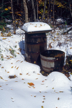 A vertical stock photo showing two water barrels fed from underground spring on a sunny winter day.