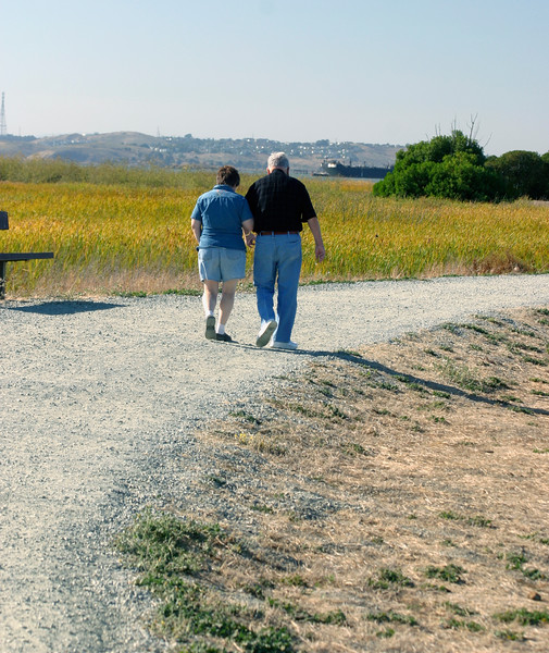 A vertical stock photo of an Elderly Father and Daughter Walking along gravel path Martinez California.