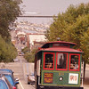 A vertical stock photograph of trolley car going down a hilly San Francisco street.