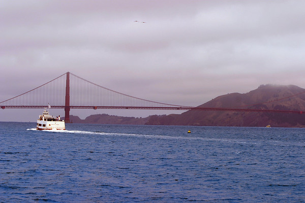 A horizontal stock photograph of a boat on San Francisco bay with San Francisco Golden Gate Bridge in the background.