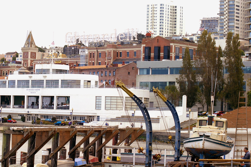 A horizontal stock photograph showing San Francisco California, Ghirardelli building. Boat yard in foreground.