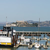 A horizontal photograph of pier 39 showing moored boats and sealions in the foreground and Alcatraz island in the background.