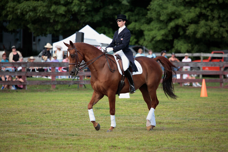 A horizontal stock Photograph of a young woman riding her horse through free style dressage steps to music.