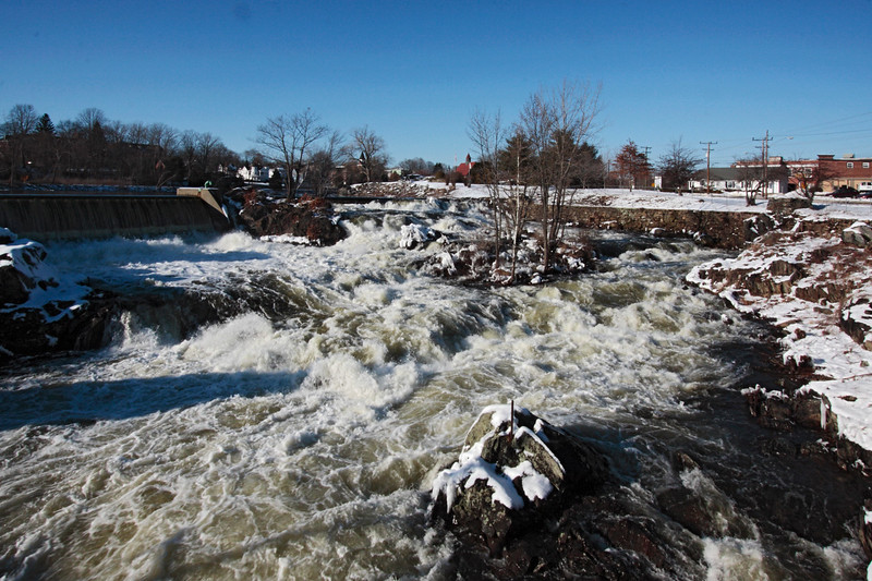A horizontal stock photo of the high water rushing over Cargill Falls in Putnam Connecticut.Photo taken on a bright sunny Winter day.