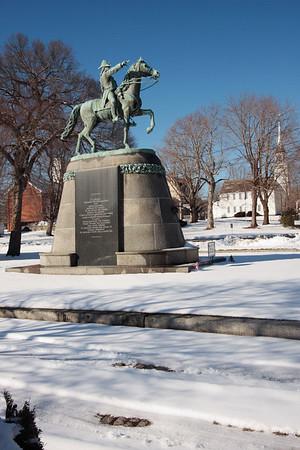 A vertical stock photo of the statue honoring Israel Putnam Esq. A Senior Major General in the Armies of the United States of America located in Brooklyn Connecticut. Photo taken on a bright sunny winter day.