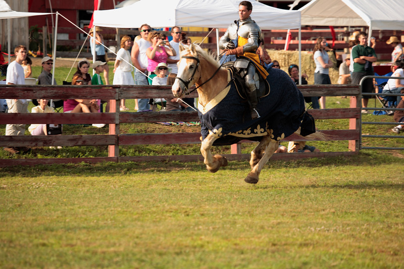 A horizontal Stock Photograph of young man dressed in full armor galloping his steed during a jousting exhibition.