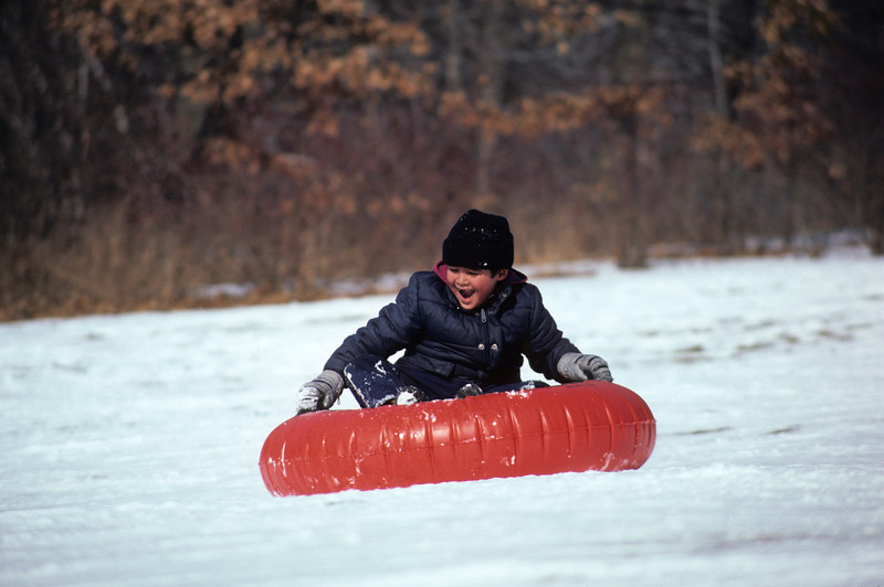 A horizontal stock photograph of a young boy sliding down the hill on a bright red snow tube.With a big smile and missing teeth.