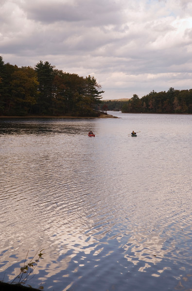 A  vertical stock photograph of two men in kayaks on a fresh water lake.A beautiful fall afternoon. at Mashapaug Lake Union Connecticut.