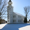 A Vertical Stock Photograph of a white church in Brooklyn Connecticut.Off Scenic Route 169.A bright sunny Winter day.