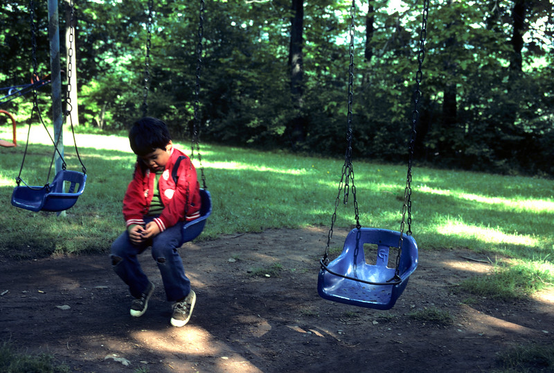 A young boy with a bright red jacket sets alone on a swing looking dejected and sad.
