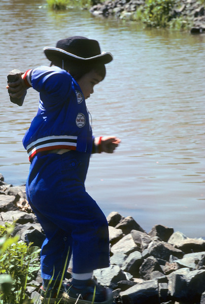 A young Filipino American boy getting ready to throw a rock into the water.