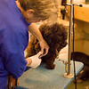 Working grooming salon showing a female groomer trimming toe nails with a dremel tool.