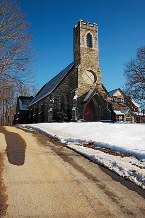 A vertical stock photo of the Trinity Parish Church in Putnam Connecticut.A beautiful historic Church. Photo taken on a bright sunny Winter day,looking up the driveway.