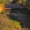 A Vertical Stock Photograph of the Comstock Covered bridge spanning the salmon River in Colchester Connecticut.Showing the bright autumn foliage.