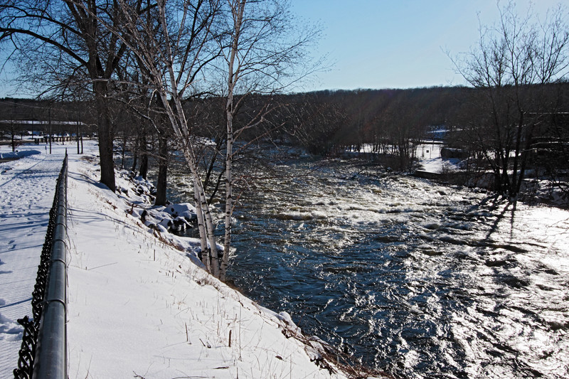 A horizontal stock photo of the Quinebaug river in Putnam Connecticut. A contrasty winter day with snow and white birch trees in the foreground.