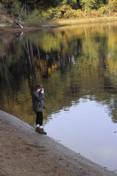 A woman stands beside a lake and photographs the fall scenery.