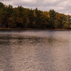 A vertical stock photograph of two people kayaking on a fresh water lake. A beautiful New England fall day.