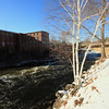 A Vertical Stock Photograph of the Quinebaug River in Putnam Connecticut. Snow and white birch tree in foreground and old textile mill in the background.