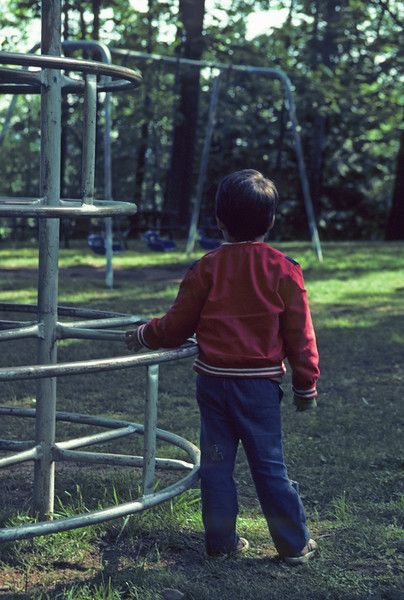 A vertical stock photograph of a young filipino american boy standing alone at a playground.